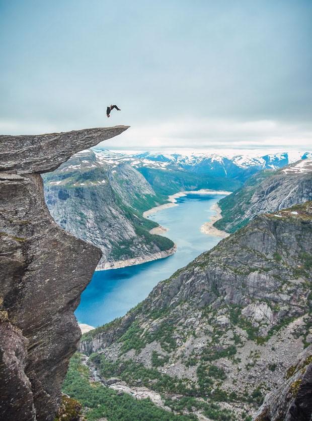 Toby Segar gira no ar em pirueta no momento em que dá um mortal para trás na rocha Trolltunga, na Noruega (Foto: Caters News/The Grosby Group)