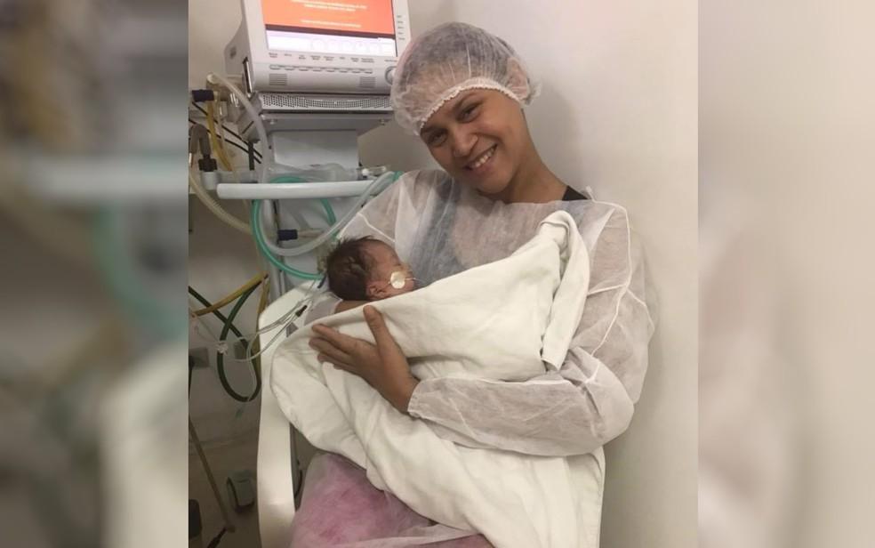 Mãe pega uma das siamesas separadas em Goiânia no colo pela primeira vez e se emociona, dizem médicos em Goiás — Foto: Facebook/Reprodução