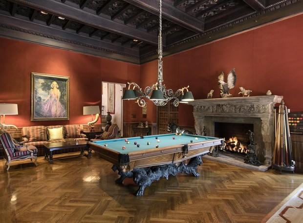 A decoração da sala de bilhar é repleta de obras de arte, com uma lareira rebuscada (Foto: Jim Bartsch/ Reprodução)