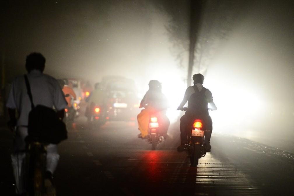 Pessoas dirigem durante tempestade de areia em Allahabad, Índia, neste domingo (13). (Foto: Sanjay Kanojia/AFP)