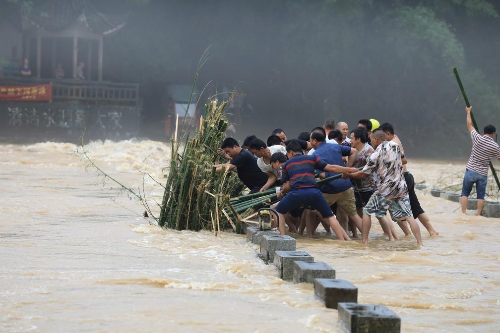 Pessoas tentam tirar bambus do caminho depois da forte chuva que atingiu a província de Guangxi, na China, nesta segunda-feira (10). — Foto:  China Daily via Reuters