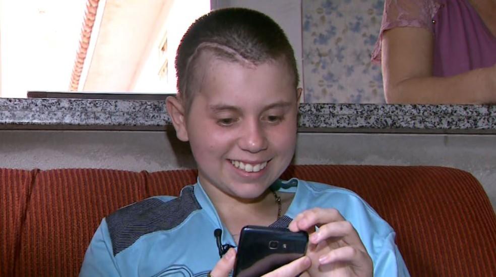Alan de Souza, de 15 anos, com celular novo que ganhou com doações em Franca (SP) (Foto: José Augusto Júnior/EPTV)