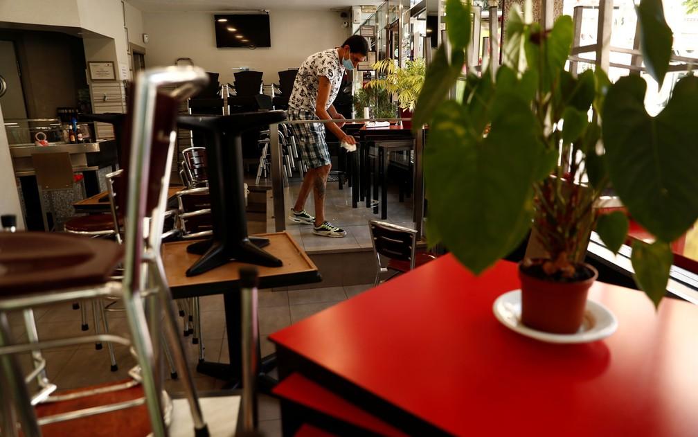 Homem usando máscara limpa mesas em restaurante em Madri, na Espanha, na sexta-feira (22) — Foto: Reuters/Susana Vera