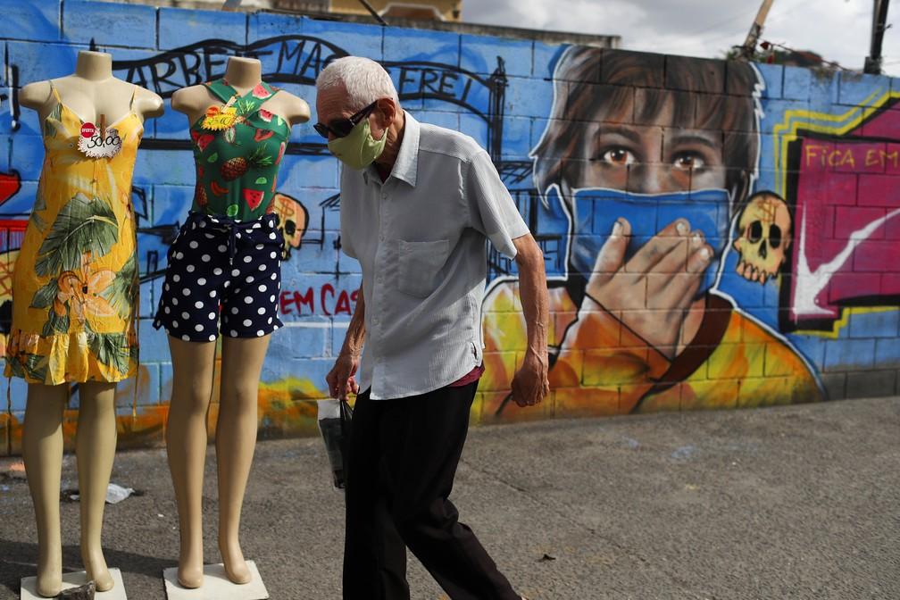 Idoso de máscara anda em frente a muro com grafite de criança com máscara contra a Covid-19 no Rio de Janeiro nesta terça (16). — Foto: Pilar Olivares/Reuters