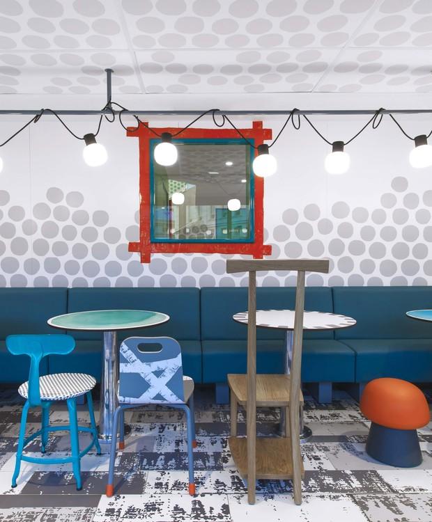 Cadeiras de diferentes tamanhos cercam as mesas, que são iluminadas por um fio de pendentes pendurados sobre uma haste de metal no teto (Foto: Dezeen/ Reprodução)