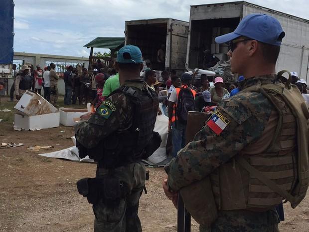 Militares chilenos e brasileiros protegem carregamentos de comida e suprimentos no sul do Haiti (Foto: BBC/Minustah)
