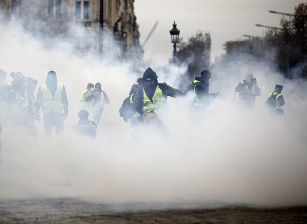Manifestantes mascarados vestindo coletes amarelos surgem em meio ao gás lacrimogêneo perto da avenida Champs-Elysees durante protesto contra aumento de impostos. — Foto: Kamil Zihnioglu/AP