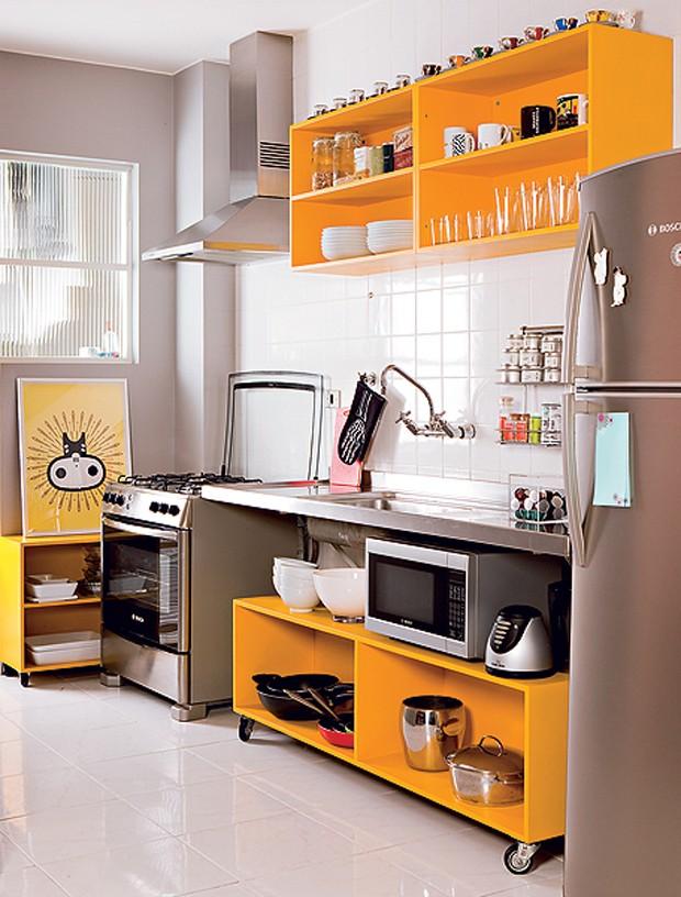 O publicitário Marcio Mota transformou os armários velhos da cozinha em módulos sem portas e laqueados de amarelo. Um está afixado na parede acima da pia e outro, com rodízios, encaixa-se embaixo da bancada (Foto: Edu Castello/Casa e Jardim)