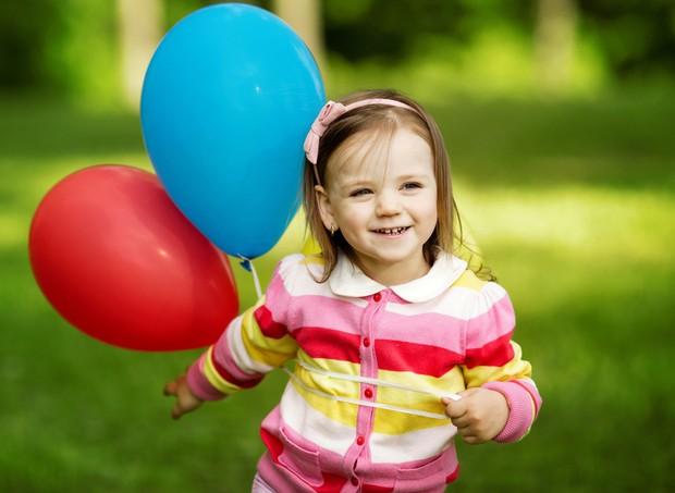 Criança segurando balões de aniversário  (Foto: Shutterstock)