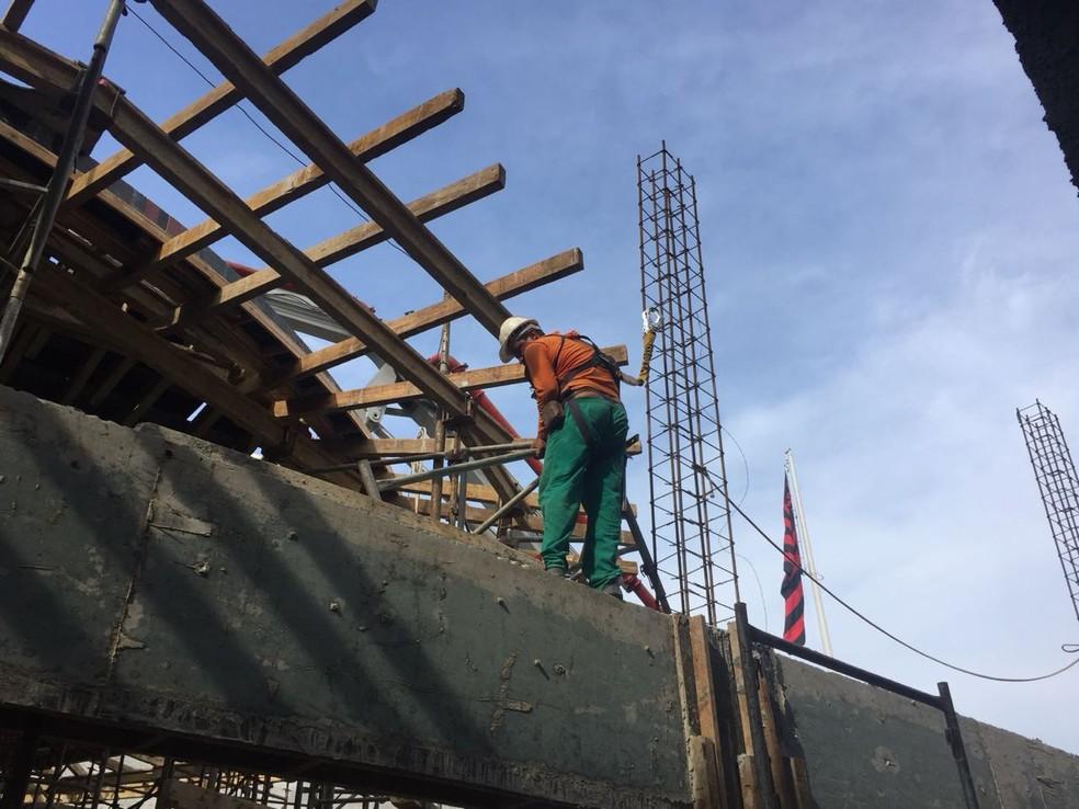 Funcionário faz ajustes na estrutura da entrada principal do novo prédio do Ninho do Urubu (Foto: Raphael Zarko)
