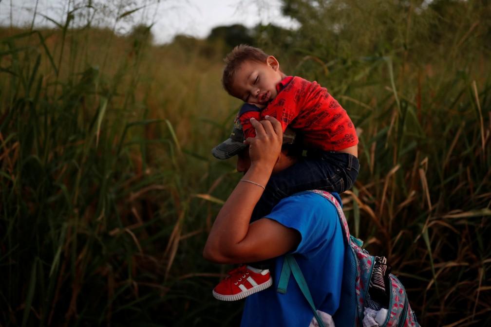 Oscar Martinez, 37 anos, migrante de Honduras, parte de uma caravana que viaja para os EUA, carrega seu filho Dilan, de 3 anos, enquanto caminham pela estrada para Huixtla, perto de Tapachula — Foto: Reuters/Carlos Garcia Rawlins