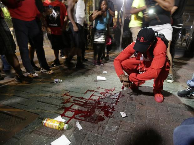 Homem é visto ao lado de poça de sangue formada após um manifestante ser baleado em Charlotte, na noite de quarta (21), durante protesto pela morte de Keith Lamont Scott (Foto: AP Photo/Chuck Burton)