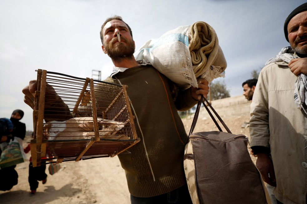 Homem carrega pertences durante saída da vila de Beit Sawa, em Guta Oriental (Foto: Omar Sanadiki/Reuters)