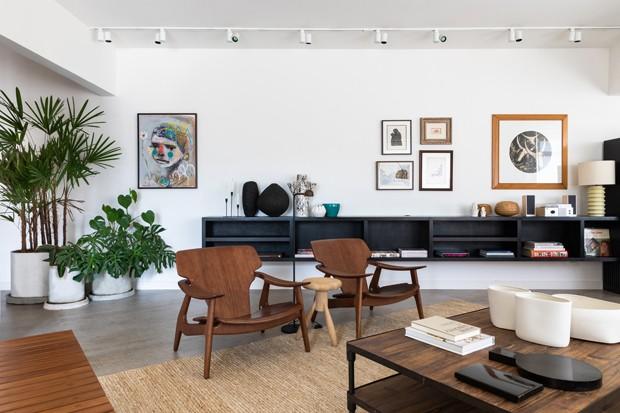 Apartamento com decoração urbana cheio de plantas e peças de design