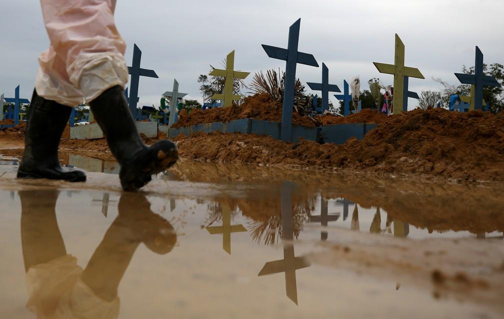 Coveiro caminha em meio a lápides de vítimas da Covid-19 no cemitério Parque Tarumã, em Manaus, em 25 de fevereiro. — Foto: Bruno Kelly/Reuters
