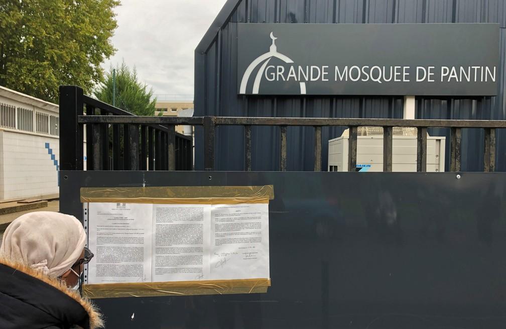 Uma mulher lê um decreto municipal instalado nos portões de entrada da Grande Mesquita de Pantin, perto de Paris, França, nesta terça-feira (20) — Foto: Antony Paone/Reuters