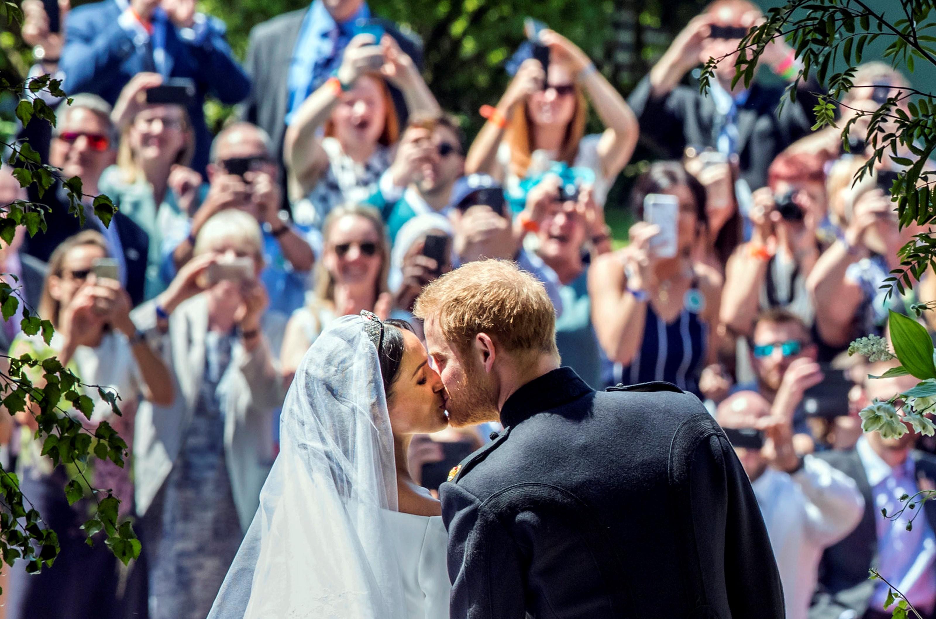 Meghan Markle e o príncipe Harry se beijam à porta da Capela de São Jorge, no Castelo de Windsor, após a cerimônia de casamento