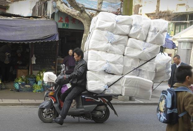 Em dezembro de 2011, um chinês foi fotografado andando em uma motoneta supercarregada em uma rua em Xangai. A carga era maior do que o próprio veículo. (Foto: Peter Parks/AFP)