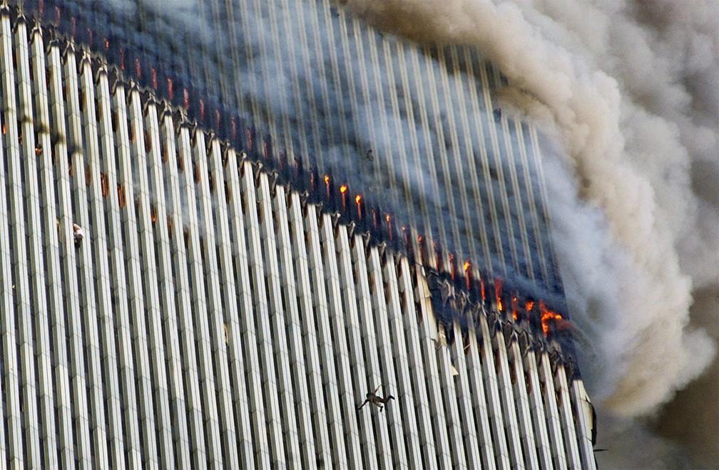 Uma pessoa é vista em queda da torre norte do World Trade Center em chamas enquanto outra se pendura do lado de fora, após os ataques aéreos do 11 de Setembro em Nova York — Foto: Richard Drew/AP/Arquivo