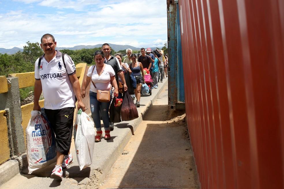 Pessoas cruzam a ponte Simon Bolívar em meio a containers que ainda bloqueiam a passagem de automóveis. — Foto: Carlos Eduardo Ramirez/Reuters