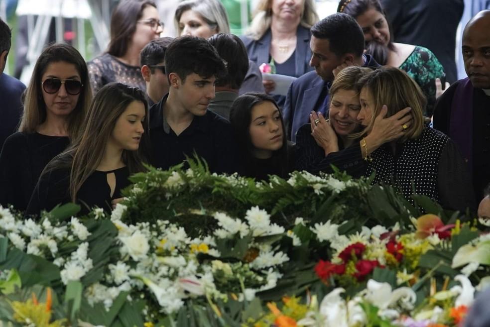 Filhos e viúva de Gugu se abraçam na despedida da família ao apresentador no cemitério. — Foto: Marcelo Brandt/G1