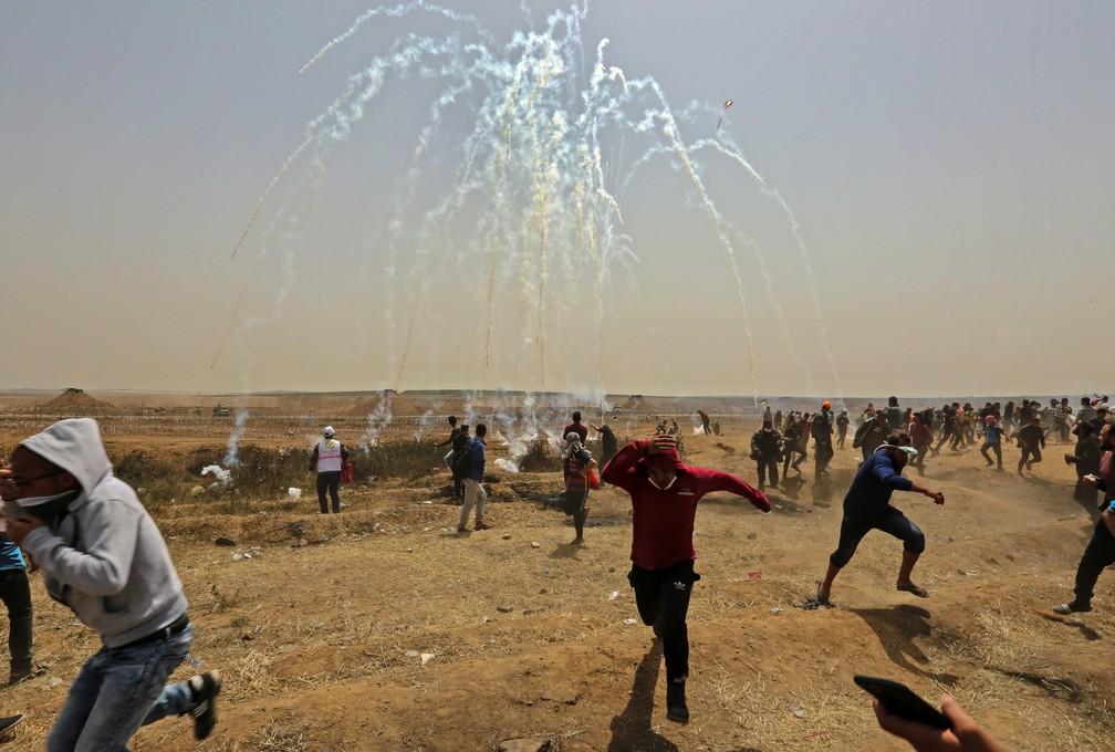 Palestinos se protegem de bombas de gás lacrimogênio durante confrontos com forças de segurança israelenses perto da fronteira de Israel, na Faixa de Gaza (Foto: Mahmud Hams/AFP)