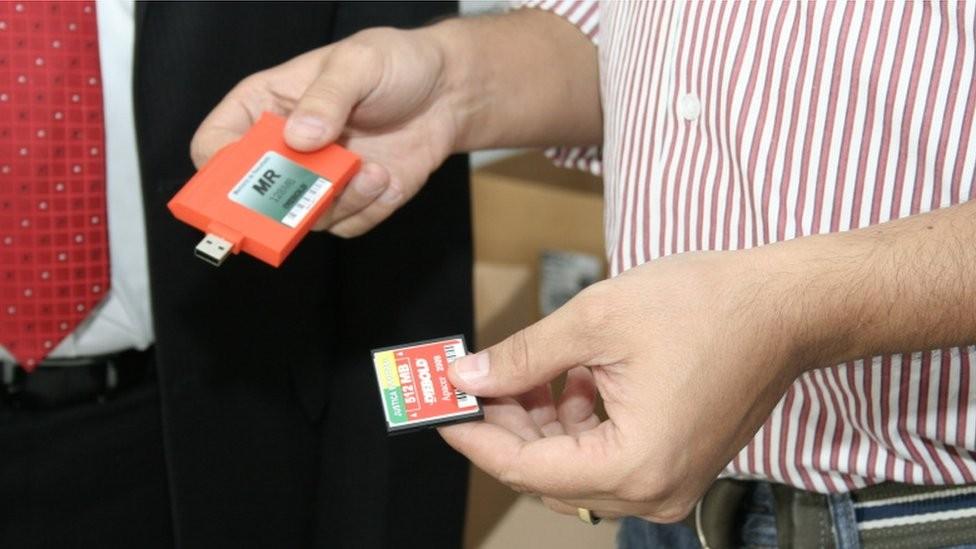 As urnas eletrônicas funcionam com uma memória flash (dir.) e os dados são transferidos para a memória de resultado (em laranja, esq.) (Foto: TRE-GO via BBC)