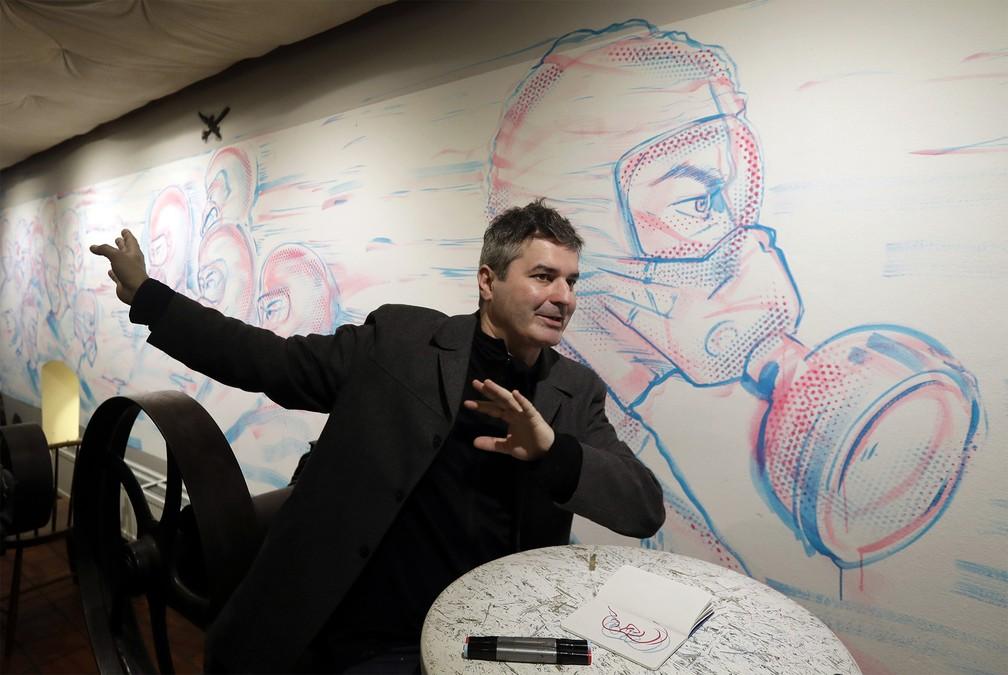 O artista tcheco Michal Cimala fala sobre seu mais recente trabalho, que consiste de pinturas inspiradas na disseminação do coronavírus, diante de algumas de suas obras exibidas nas paredes de um café em Praga, na República Tcheca. Foto de 12 de março — Foto: Petr David Josek/AP