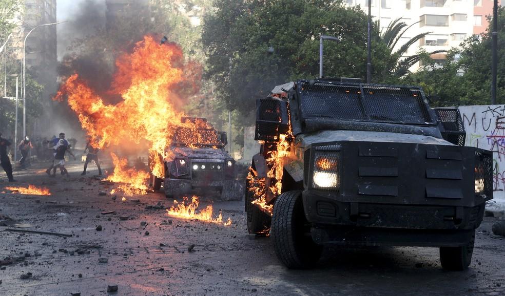 Veículos blindados da polícia foram incendiados em confronto neste domingo (18) em Santiago — Foto: Esteban Felt/AP
