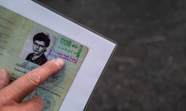 Andreas Falge mostra cópia de página do passaporte a ida a Berlim Ocidental, com carimbo de saída em 1º de outubro de 1989