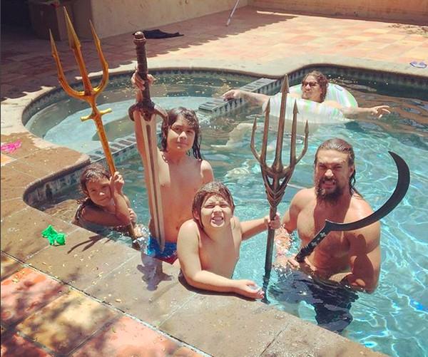O ator Jason Momoa brincando em uma piscina com os filhos e amiguinhos enquanto uma das crianças com as armas do herói Aquaman (Foto: Instagram)