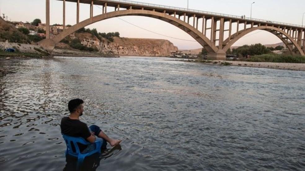 Calma antes da tormenta: um homem descansa nas margens do rio Tigre, enquanto as águas sobem lentamente para submergir seu povoado — Foto: Getty/ BBC