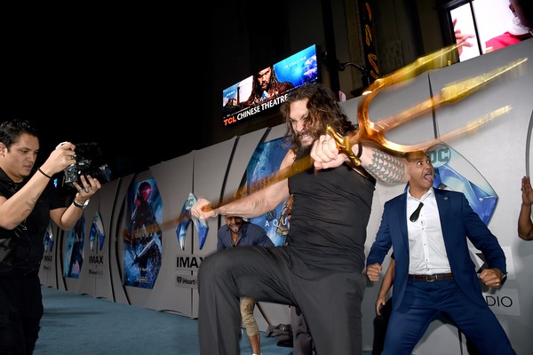 O ator Jason Momoa com o tridente do herói Aquaman no evento de lançamento do filme do personagem da DC Comics (Foto: Getty Images)