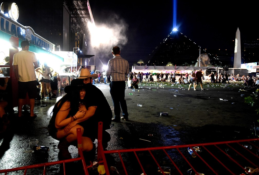 Casal se protege após tiros serem disparados sobre multidão em um festival de música country em Las Vegas, nos EUA (Foto: David Becker/Getty Images/AFP)