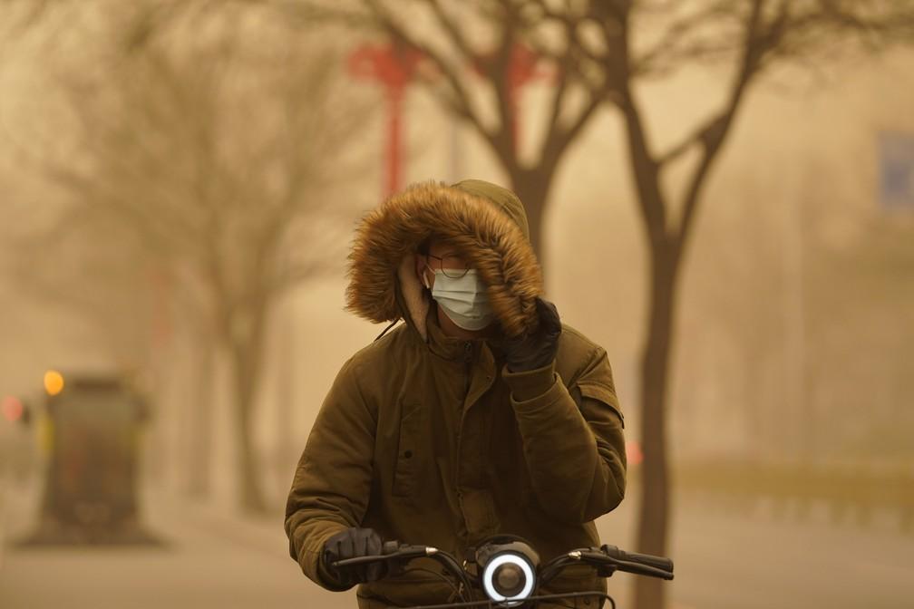 Ciclista tenta cobrir o rosto em meio a tempestade de areia que tomou Pequim nesta segunda (15) — Foto: Ng Han Guan/AP