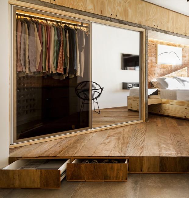 Quarto | O piso em madeira de demolição elevado 20 cm salienta a divisão entre área íntima e living. O armário em pinus maciço foi desenhado pelo escritório Tripper Arquitetura. O concreto veio para combinar com o estilo industrial do loft. Toda a marcena (Foto: Julia Ribeiro/Divulgação)
