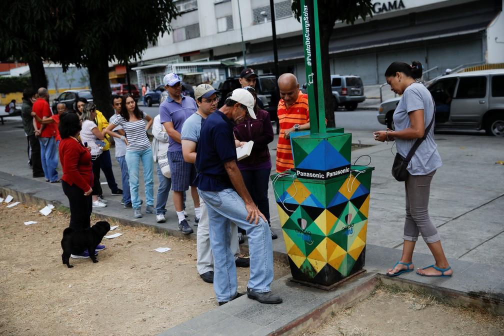 Venezuelanos tentam carregar celular utilizando painel solar — Foto: Reuters