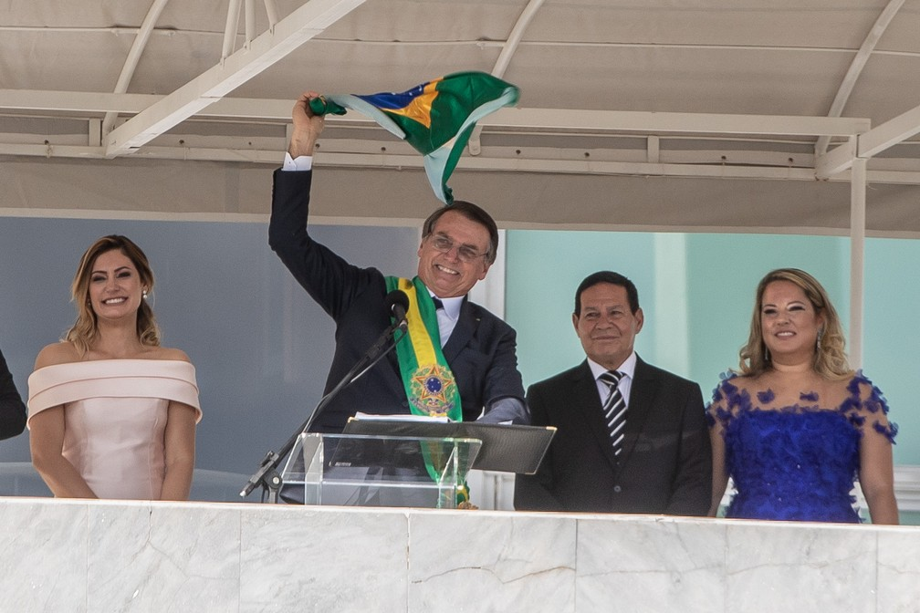 O novo presidente do Brasil, Jair Bolsonaro, gira no ar uma bandeira do Brasil ao lado de sua esposa, Michelle Bolsonaro, após receber a faixa presidencial do ex-presidente Michel Temer, no Palácio do Planalto, em Brasília — Foto: Fábio Tito/G1