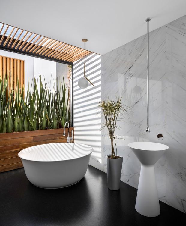 No banheiro, um pergolado fica abaixo do teto e janela de vidro, causando sobras horizontais sobre a banheira (Foto:  Rafael Gamo/ Reprodução)
