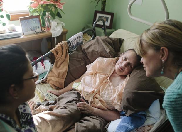 A universitária Cindy (à esquerda) e a coordenadora Kelly Keane (à direita), em visita à Martha Keochareon, vítima de um câncer terminal (Foto: Ilana Panich-Linsman/The New York Times)