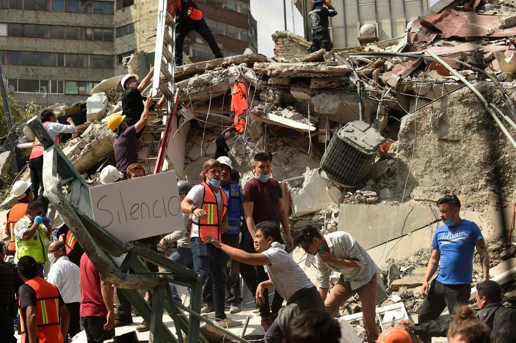 Pessoas que trabalhavam no resgate mostram um cartaz com o pedido de silêncio, na tentativa de encontrar sobreviventes após terremoto que atingiu o México, na terça-feira (19)  (Foto: Pedro Pardo / AFP)