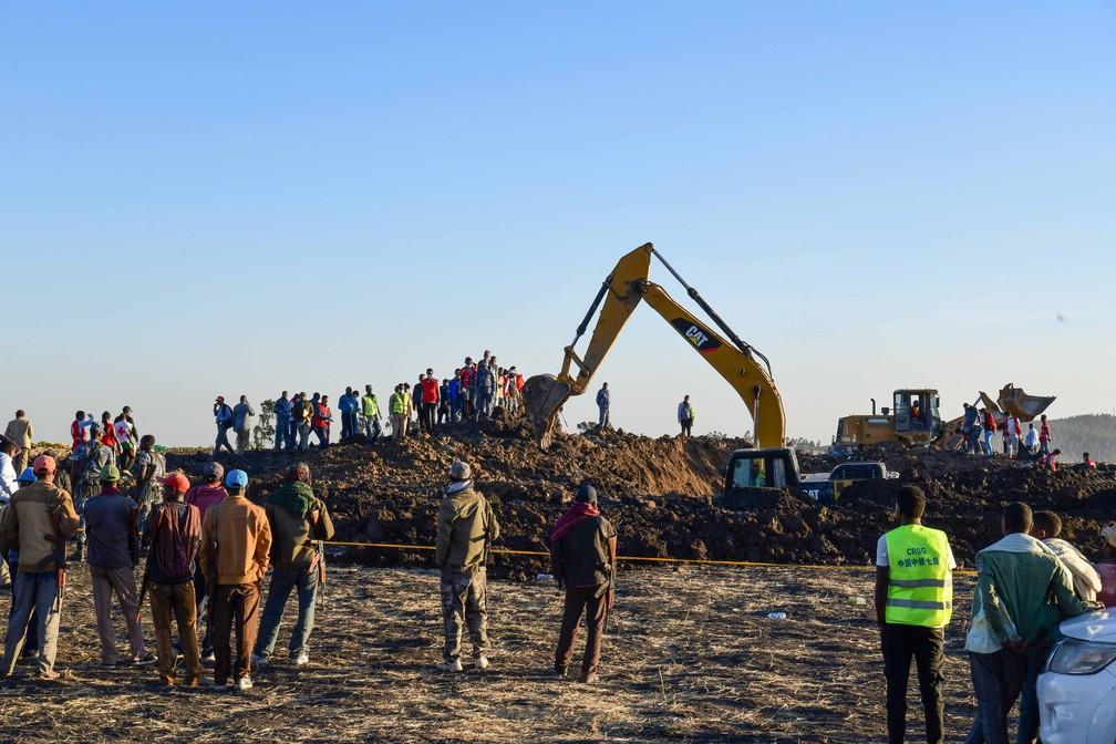 Trabalho da equipe da Cruz Vermelha em meio a destroços no local do acidente com avião na Etiópia — Foto: Michael Tewelde / AFP