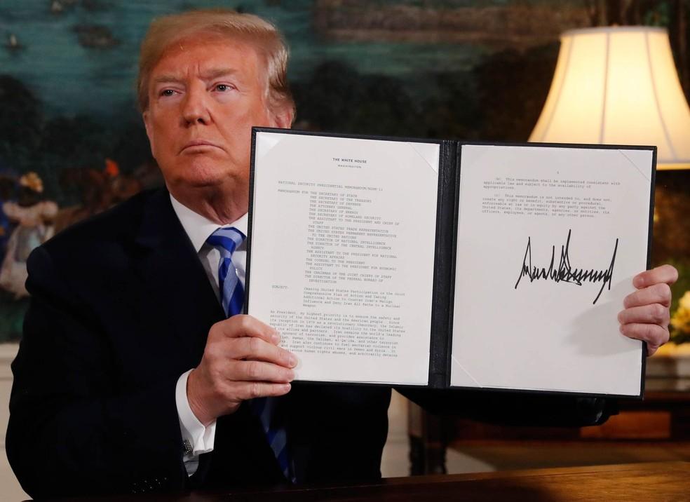 Presidente dos EUA, Donald Trump, mostra sua assinatura oficializando a retirada do país do acordo nuclear com o Irã — Foto: Jonathan Ernst/Reuters