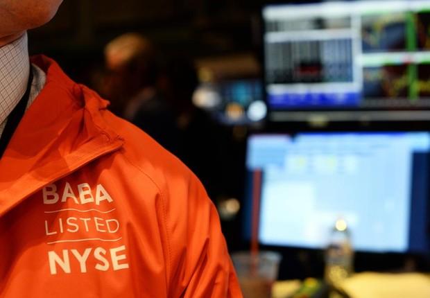 Operador com jaqueta do Alibaba em dia de pregão de ações de tecnologia (Foto: Getty Images)