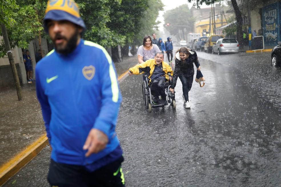 Torcedor cadeirante tenta chegar à Bombonera, enfrentando o alagamento nas ruas próximas ao estádio — Foto: Reuters