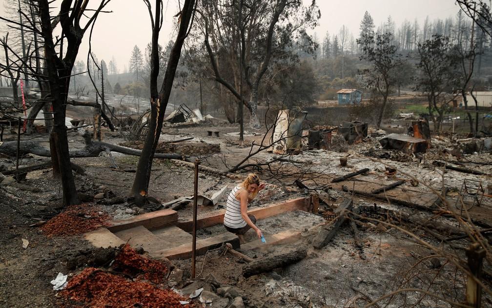 -  Bree Seville usa um pequeno pincel para procurar objetos em meio às ruínas da casa da mãe de seu noivo, destruída por incêndio na região de Redding,