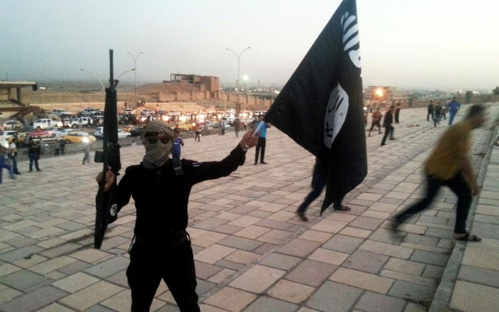 Combatente do Estado Islâmico exibe arma e bandeira do grupo em rua de Mossul, no Iraque, em foto de 23 de junho de 2014 (Foto: Reuters/Stringer)