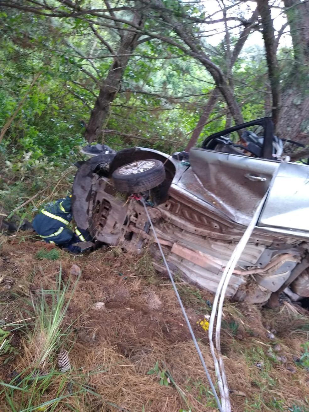 Carro parou de lado em árvore após sair da pista e capotar e bombeiros precisaram usar guincho pra desvirar veículo  — Foto: Corpo de Bombeiros Militar/Divulgação