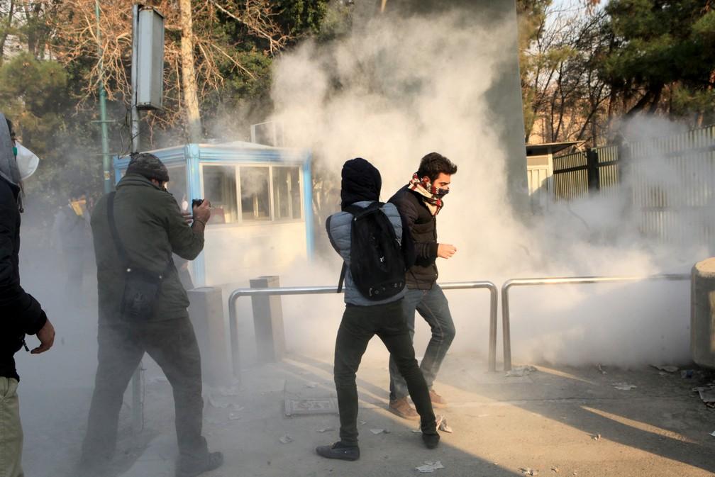 Polícia lança gás lacrimogêneo contra estudantes que protestavam neste sábado (30) na Universidade de Teerã (Foto: STR / AFP)