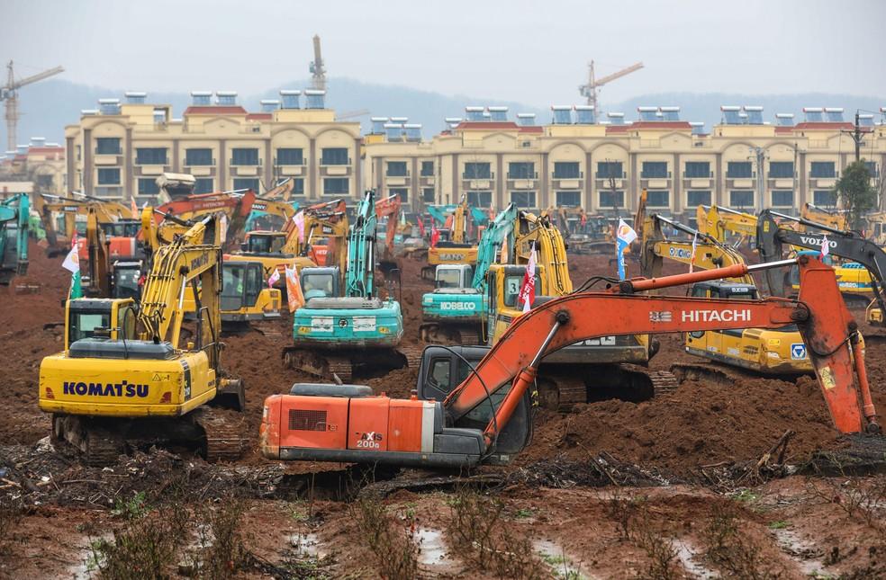 Escavadeiras trabalham em área de hospital em Wuhan, na China. Nova estrutura de saúde deve ter 1 mil leitos. — Foto: STR/AFP